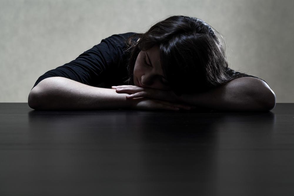 Pensive and sad girl putting her head on the table, horizontal-1